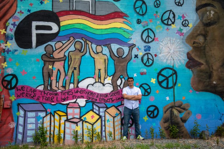 An image of Joel Brooks in front of a mural.